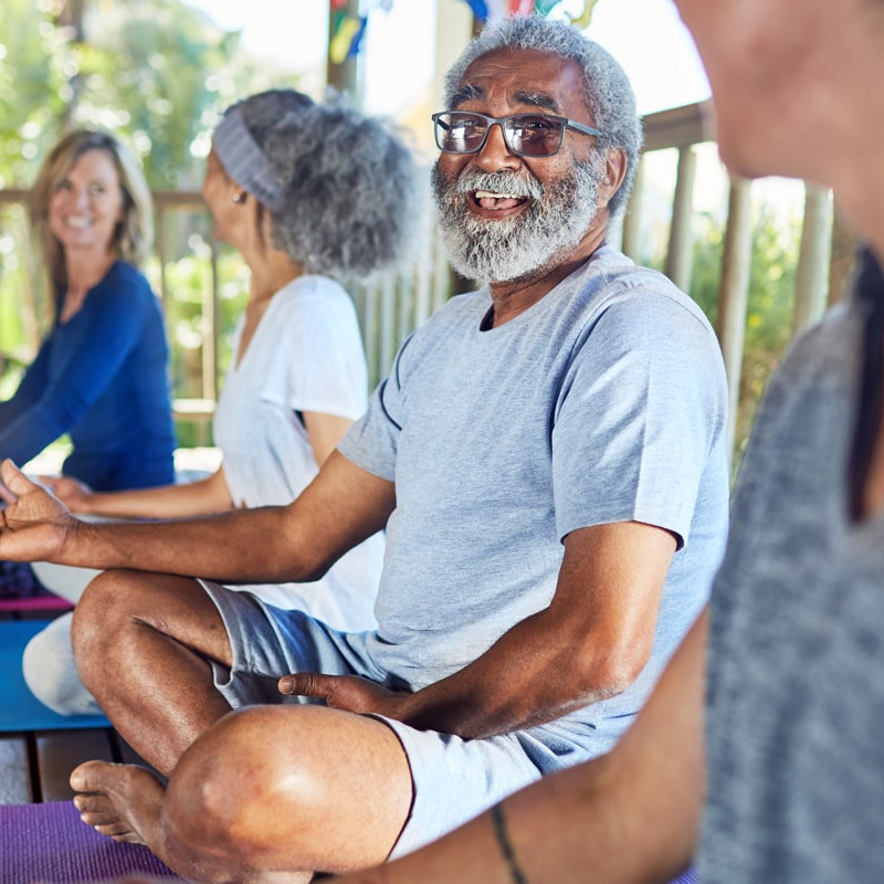 Group of seniors sitting on yoga mats outside on a porch in a meditation sitting position laughing.