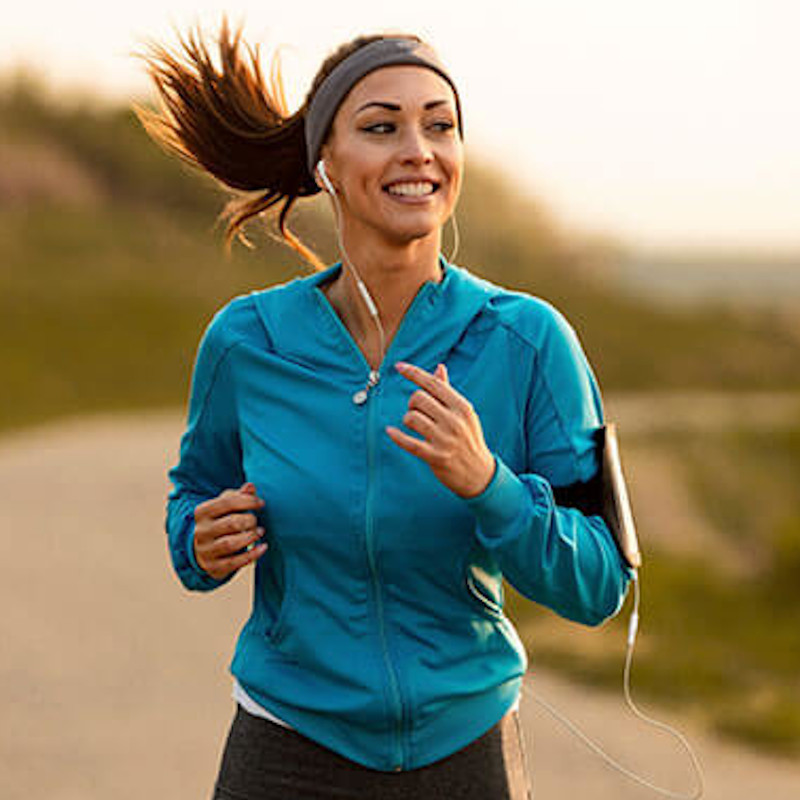 Women jogging outdoors in a blue jacket with headphones while smiling.