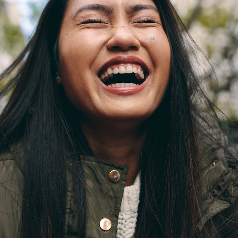 Closeup photo of a women laughing with eyes closed.